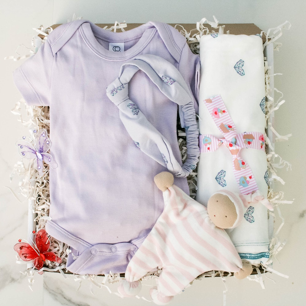 Oh, It's a Baby Girl gift basket that contains an Under the Nile Baby Buddy, Classic Bodysuit, Swaddle Blanket, Brielle Headband